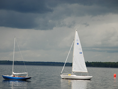 Two sailboats idle under a darkened sky